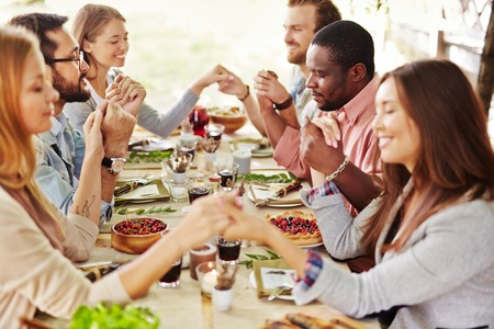 Grupp unga vänner be vid Thanksgiving bord Stockfoto