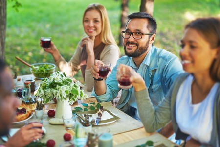Happy Asian man with glass of red wine sitting at Thanksgiving party Stock Photo