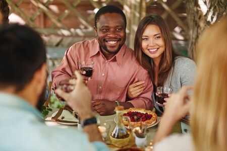 thanksgiving dinner: Happy young couple with red wine sitting by Thanksgiving table