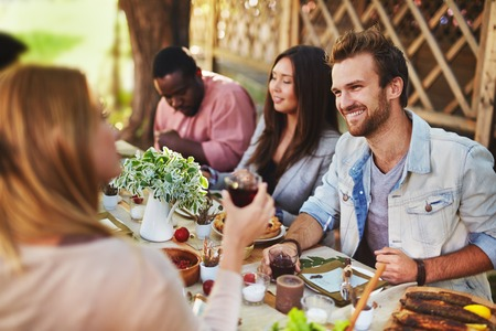 adult group: Happy young man talking to girl at Thanksgiving party Stock Photo