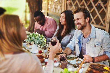 amigos: Hombre joven feliz de hablar con chica en la fiesta de Acci�n de Gracias