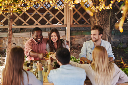 Happy young couple offering their friends traditional food by Thanksgiving table Stock Photo