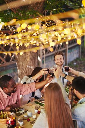 AMIGOS: Amigos felices que tuestan con el vino tinto en la fiesta de Acci�n de Gracias Foto de archivo
