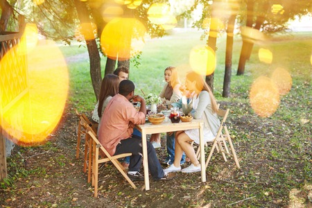 holiday gathering: Group of friends sitting by Thanksgiving table outdoors