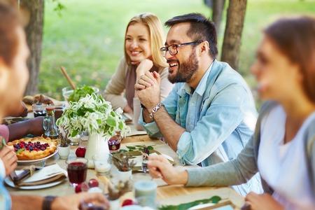 Šťastný asijské muž v brýlích a casualwear sedí u stolu díkůvzdání