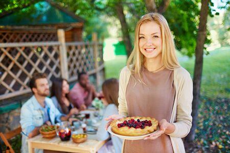 personas mirando: Mujer joven feliz con la empanada de la baya mirando a la cámara en el fondo de sus amigos, sentado junto a la mesa de Acción de Gracias
