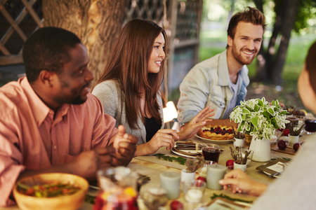 amigos: Mujer joven feliz que se sienta junto a la mesa de Acción de Gracias entre sus amigos