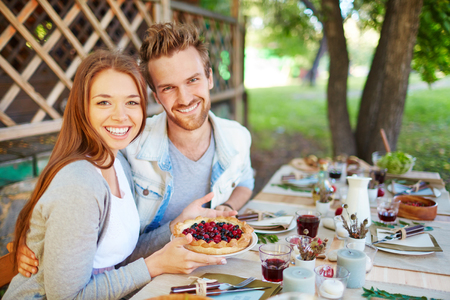 thanksgiving adult: Amorous couple looking at camaera while sitting by Thanksgiving table Stock Photo