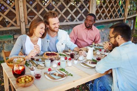 Lyckligt ungt par pratar med sina vänner på Thanksgiving fest