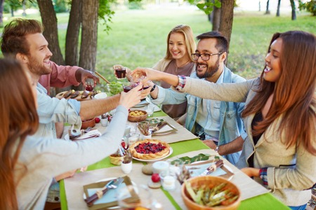 thanksgiving food: Happy friends cheering up at Thanksgiving party outdoors