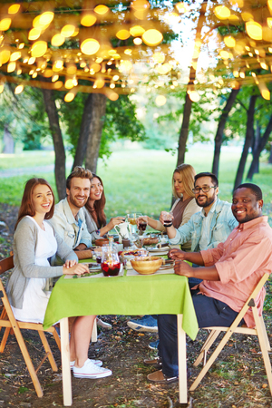 thanksgiving adult: Happy friends sitting by Thanksgiving table and looking at camera outdoors Stock Photo