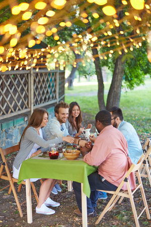thanksgiving adult: Happy friends eating Thanksgiving dinner outdoors Stock Photo