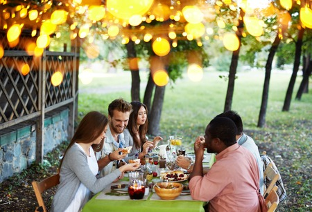 happy feast: Group of young friends having traditional dinner on Thanksgiving Day Stock Photo