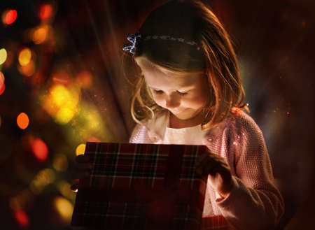 wonder: Pretty girl looking into open giftbox on Christmas day
