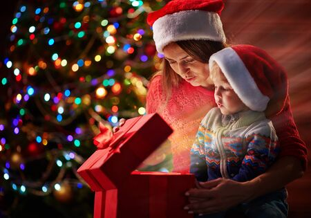 boy lady: Cute boy and his mother in Santa caps looking at light in giftbox