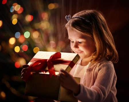wonder: Cute girl looking into open giftbox with magic light