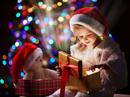 child portrait: Curious girl putting her hand into open giftbox to touch unusual Christmas present