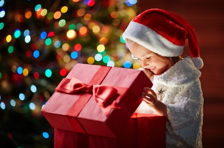 opening gift: Curious girl in Santa cap looking into open giftbox with unusual present Stock Photo