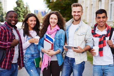 colegios: Estudiantes universitarios felices en ropa casual mirando a la cámara al aire libre
