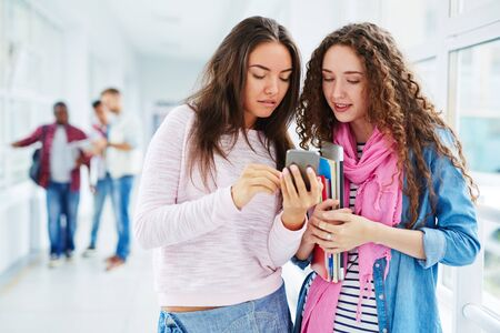 young group: Teenage girls with cellphone interacting during break