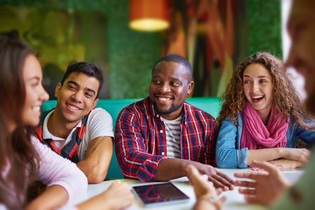 カフェに座っているとのニュースを議論する幸せな 10 代の若者