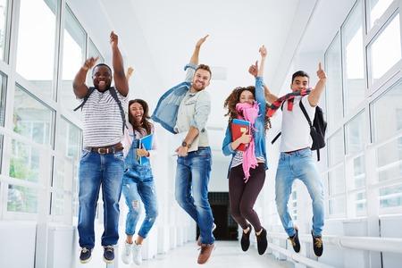 Rij van vrolijke studenten in sprong kijken naar de camera op de universiteit