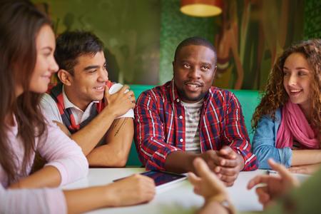 カフェで話しているフレンドリーな十代の若者たち 写真素材