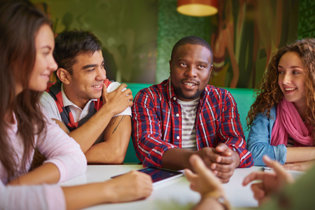 group of young people: Friendly teens talking in cafe Stock Photo