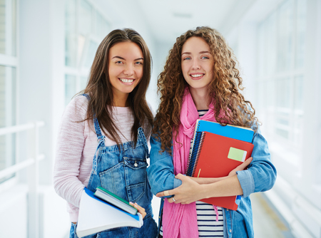learners: Happy teenage learners with books looking at camera Stock Photo