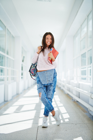 learner: Pretty student with backpack and books standing in college corridor
