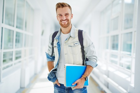Handsome student with books looking at camera in college