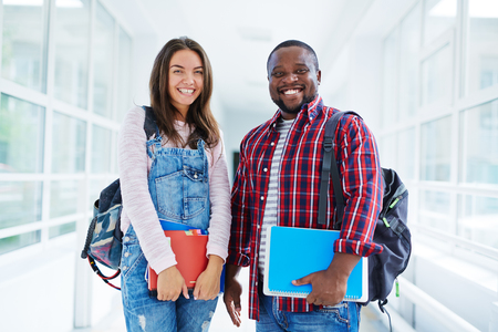 learners: Couple of modern teenage learners looking at camera in college
