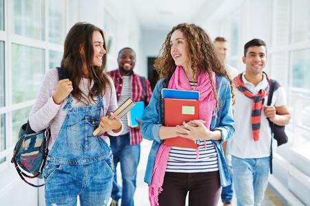 두 귀여운 학생들이 대학 복도를 따라 걷고 수업 후 이야기 스톡 콘텐츠