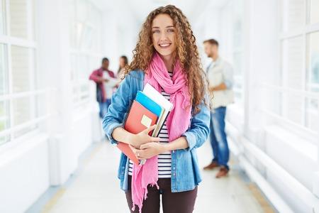 chicas sonriendo: Estudiante sonriente con los libros de pie en el pasillo de la universidad con sus amigos en el fondo