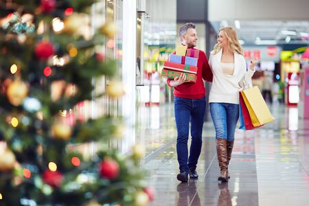 people walking: Happy couple looking for Christmas presents in the mall