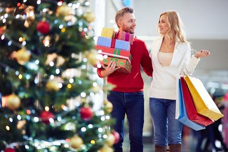 comprando: Pareja cari�osa llevando regalos de Navidad mientras que las compras en el centro comercial Foto de archivo