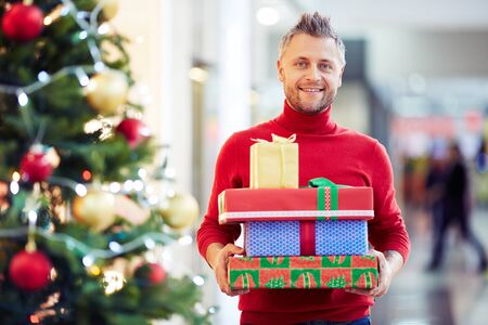 hombres maduros: Happy man with Christmas presents looking at camera Foto de archivo