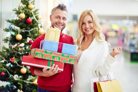 shopping spree: Affectionate couple of shoppers with Christmas gifts looking at camera Stock Photo