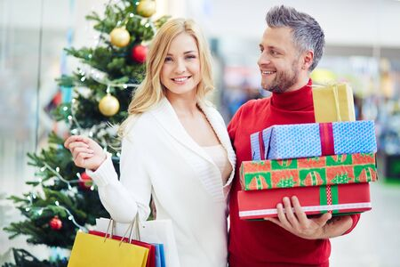 consumerism: Happy shoppers with Christmas gifts standing by decorated firtree Stock Photo