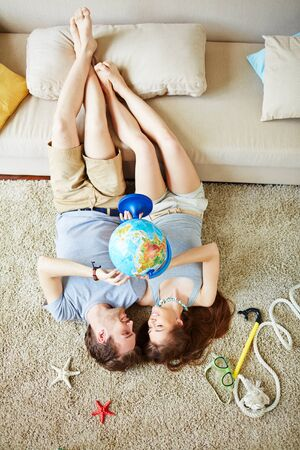 travel woman: Young man and woman with globe looking at one another while lying on the floor and making plans for summer Stock Photo