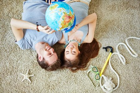 couples in love: Young couple pointing at globe while dreaming of summer vacations Stock Photo