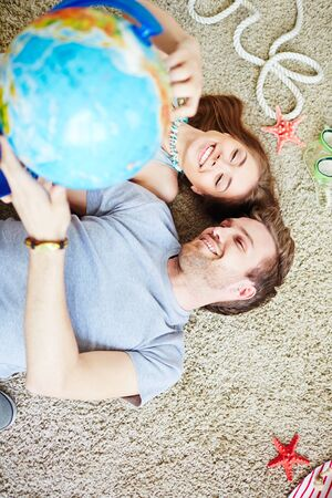 adventurers: Smiling couple of adventurers pointing at globe while lying on the floor Stock Photo