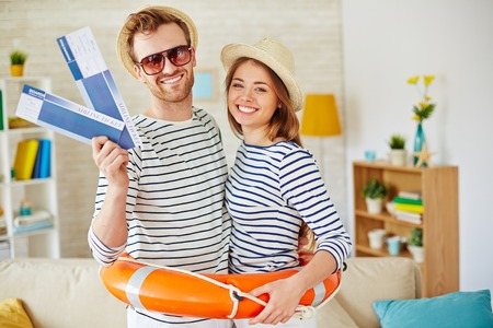 Happy couple with airline tickets and buoy looking at camera