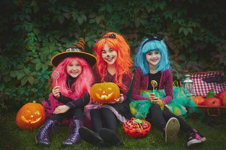 niños sonriendo: Muchachas felices con calabazas y dulces celebrar Halloween al aire libre