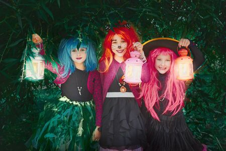 halloween: Little girls in wigs and Halloween costumes holding lanterns and looking at camera Stock Photo