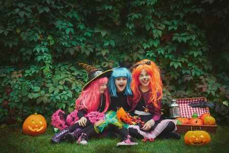 repent: Group of cute girls in wigs and Halloween costumes sitting on green grass and looking at camera