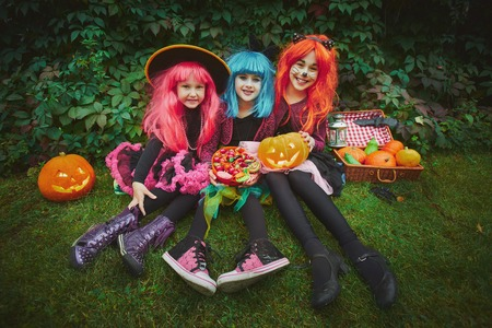 wigs: Happy girls in wigs and Halloween costumes holding pumpkins and sweets
