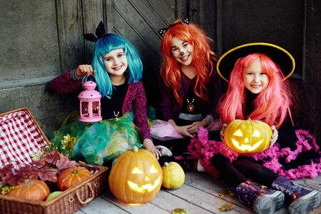Little girls with lanterns and gourds looking at camera on Halloween night