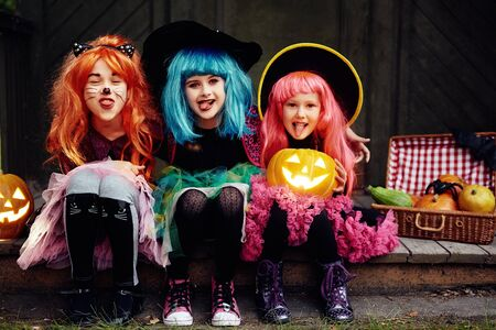 repent: Funny girls showing tongues and looking at camera on Halloween night