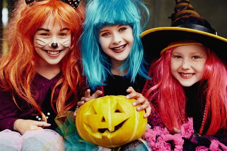 Group of girls in Halloween costumes looking at camera with smiles Stock Photo
